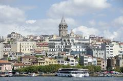 Bosphorus in front of buildings in city against sky Stock Photos