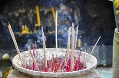 Smoke emitting from incense sticks in container at temple - stock photo