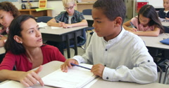 Teacher helps schoolboy in class, close up, shot on R3D Stock Footage