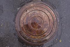 Closeup photo of Old Sewer rust manhole cover on the urban asphalt road. Rain Stock Photos