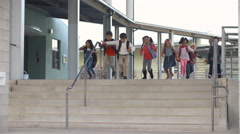 A group of energetic elementary school kids leaving school Stock Footage