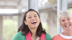 Panning shot of laughing teachers after school Arkistovideo