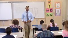 Happy black male teacher walking through class toward camera Stock Footage