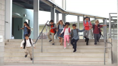 Young school kids jumping down steps as they leave school Stock Footage