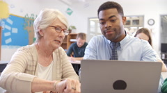 Senior female teacher helps student in adult education class - stock footage