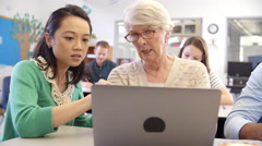 Teacher and senior pupil use laptop in adult education class - stock footage