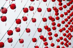 Tilt image of red Chinese lanterns hanging against sky - stock photo