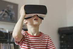 Boy wearing virtual reality simulator at home - stock photo