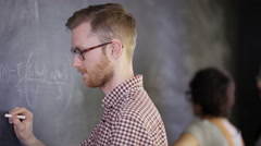4K Young intelligent college student writing mathematical equation on blackboard Stock Footage