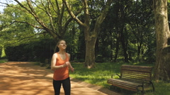 Jogging woman running in city park in sunshine on beautiful summer day Stock Footage