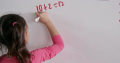 Elementary schoolgirl doing maths on whiteboard, back view Stock Footage