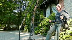 Slow motion. Adult man rides a swing in summer day Stock Footage
