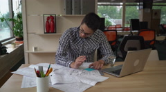 Man working with blueprint architectural sketch in the design agency Stock Footage