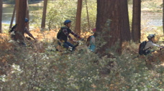 Family riding mountain bikes through a forest, panning shot Stock Footage