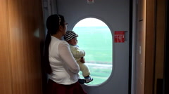 A mother holding her babe stands next to a window of a CRH train Stock Footage