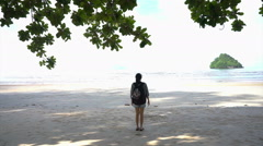 Girl standing under shadow at horizon tropical ocean beach background Stock Footage