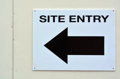 Arrow sign to site entry Stock Photos