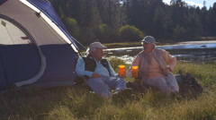 Senior couple sitting outside tent near lake, closer-in shot Stock Footage