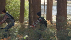 Couple talk as they ride mountain bikes in forest, tight pan Stock Footage