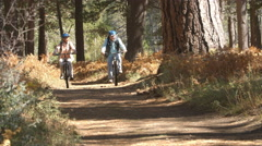 Senior couple riding bikes on a forest trail, handheld shot Stock Footage