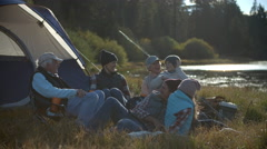 Multi generation family relaxing outside tent in countryside - stock footage