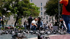 Kissing couple surrounded by flock of pigeons in Placa de Catalunya, Barcelona Stock Footage