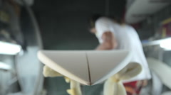 A worker in a surfboard shaping room Stock Footage