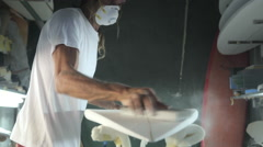 Close up sanding the bottom of a surfboard being shaped Stock Footage
