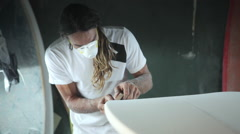 Surfboard shaping, Shaper sanding the rails of the surfboard Stock Footage