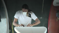 Surfboard shaping, Shaper using a foam sander to shape the bottom of the surfboa Stock Footage