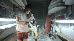 Surfboard shaping, shaper sanding the side of the blank surfboard Stock Footage