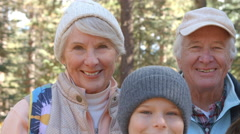 Grandparents and grandkids in forest, handheld close up shot Stock Footage