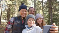 Boy taking family selfie in a forest with smartphone Stock Footage