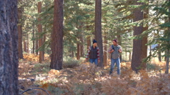 Panning shot of couple walking past on a forest trail - stock footage
