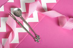 Modern sixties pink and white chevron stripe dining table setting. - stock photo