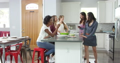 Female friends socialising in a kitchen, shot on R3D Stock Footage