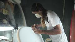 Surfboard shaping, Shaper using a foam sander to shape the side of the surfboard Stock Footage