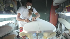 Surfboard shaping, Shaper sanding the nose of the surfboard with a block Stock Footage