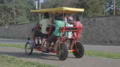 Multi-person pedal bike car takes trip 'round the park Stock Footage
