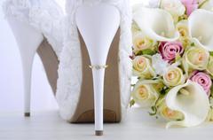 Wedding ring on beautiful white stiletto shoe heel. Stock Photos