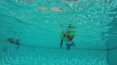 Underwater shot kids swimming in an outdoor pool Stock Footage