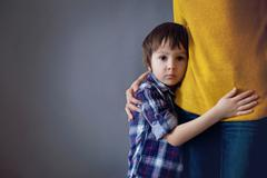 Sad little child, boy, hugging his mother at home - stock photo