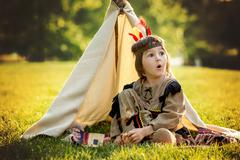 Cute portrait of native american boy with costumes, playing outdoor in the pa - stock photo