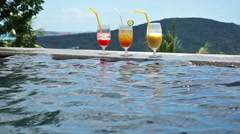 Young mixed couple swimming in the pool cocktail glasses in background Stock Footage