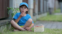 Sweet adorable little child, boy eating strawberries, summertime. Kid eating  Arkistovideo