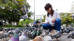 Woman feeding flock of pigeons in Placa de Catalunya, Barcelona, slow motion Stock Footage
