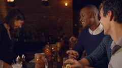 Male Friends Enjoying Night Out At Cocktail Bar, Slow Motion Stock Footage