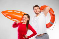 lifeguard couple with rescue equipment - stock photo