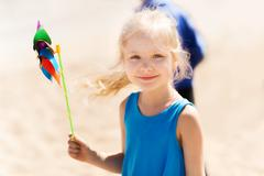 Happy little girl with colorful pinwheel at summer Stock Photos