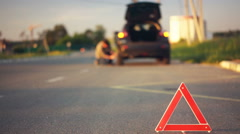 Road hazard triangle on road, unlucky driver changing flat tyre, car breakdown - stock footage